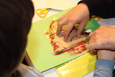 Criança e adulto a fazerem o postal com o contorno de Árvore de Natal