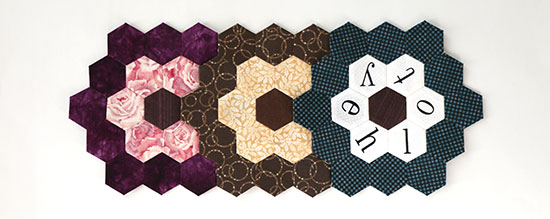 Three overlapping hand sewn hexagon flower blocks lined up horizontally in purples, browns, and blues, on a white background.