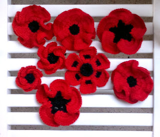 A variety of crocheted poppy flowers displayed on a white striped background
