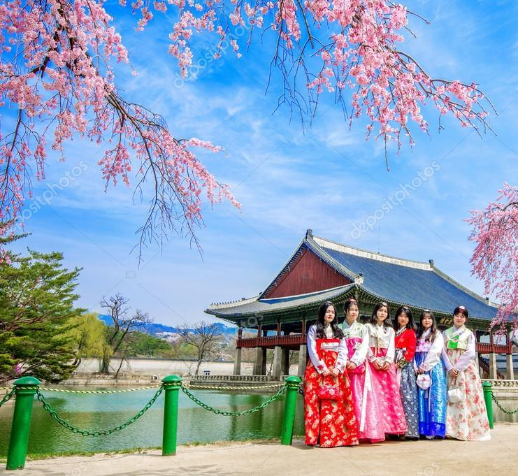 Gyeongbokgung Palace (경복궁) with cherry blossom in spring and tourists with dress Hanbok
