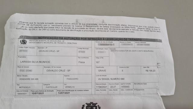 Mulher leva multa de infração grave de trânsito no valor de R$ 195,23 por falta de uso de cinto de segurança na condução de motocicleta