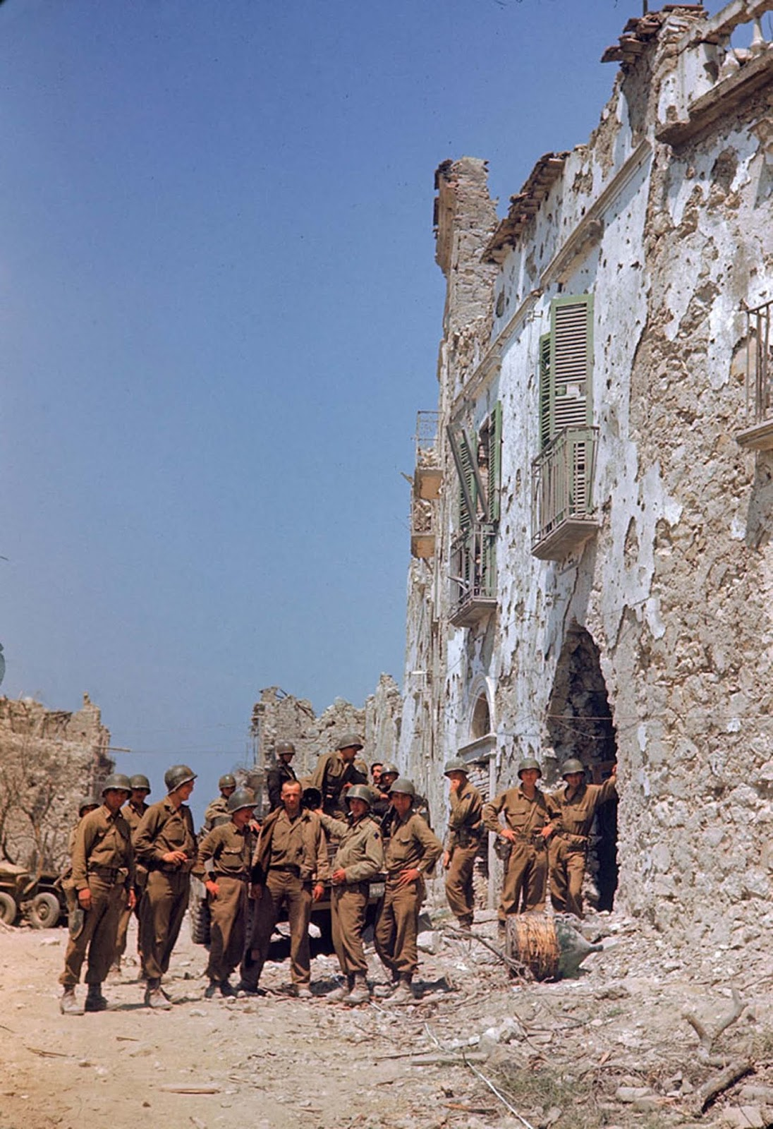 American troops stood in front of a bombed-out building during the drive towards Rome, WWII.