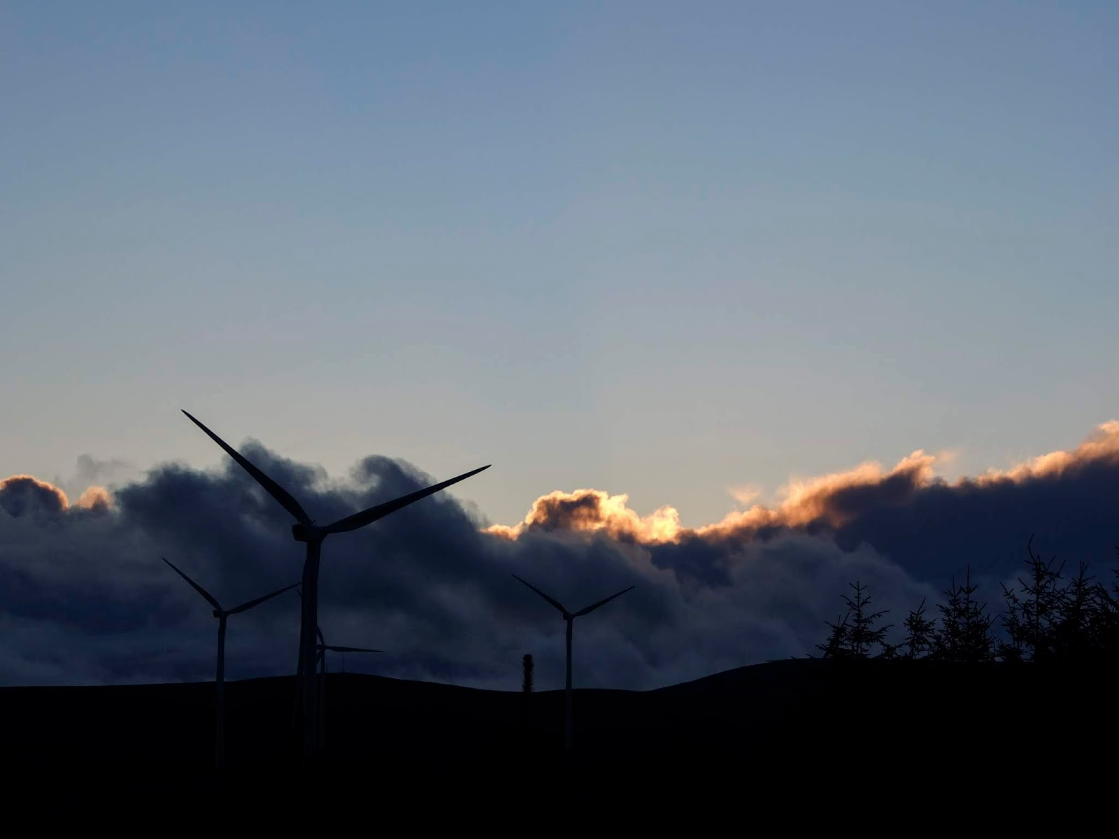The last of sunset clouds behind the windmills and mountains in North Cork.