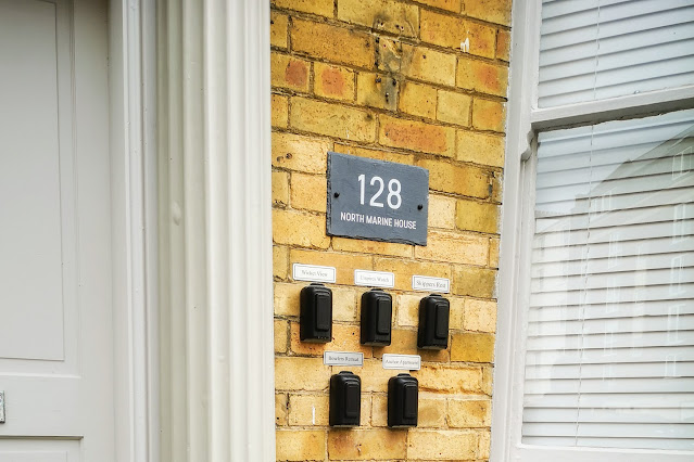 Image of the building that houses Skippers Rest. Image shows the key pad access that is required to check in to the apartment. The front door to the communal hallway and a window into one of the apartments with white blinds.