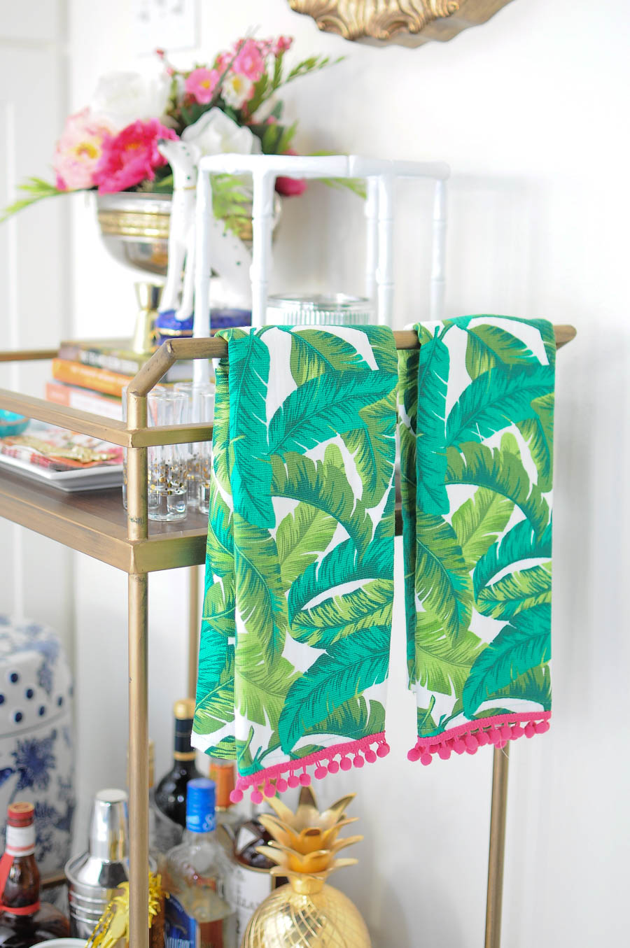Palm towels add a Palm Beach vibe to a gold bar cart decorated for spring with flowers, candles, and other gorgeous decor accents.