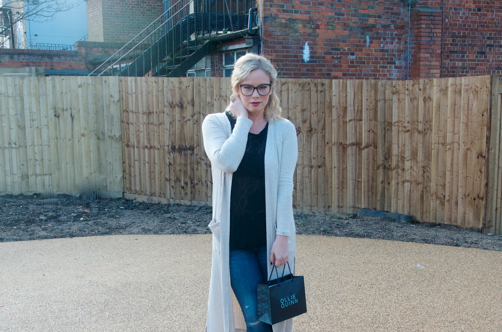 Long cream cardigan, black eyelet top, distressed blue jeans and black round rimmed glasses with ollie quinn shopping bag