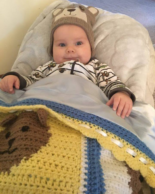 Front view of baby tucked into the teddy bear blanket. Baby is wearing a two-tone brown beanie with a teddy bear's face embroidered on the front and teddy bear ears attached to the top seam. Baby is looking straight at the camera. He is wearing a zip up jumpsuit, white with dark, narrow, horizontal stripes and pictures between. The sleeve cuffs are wider and dark coloured. The teddy bear blanket is folded back at the top to show the light blue satin lining next to baby. The blanket's yellow border can be seen with a white ribbon woven along the inside edge. At the bottom of the photo is a yellow square with a teddy bear face (left) and part of a white square with a teddy bear face (right). The squares are separated by a vertical blue stripe.