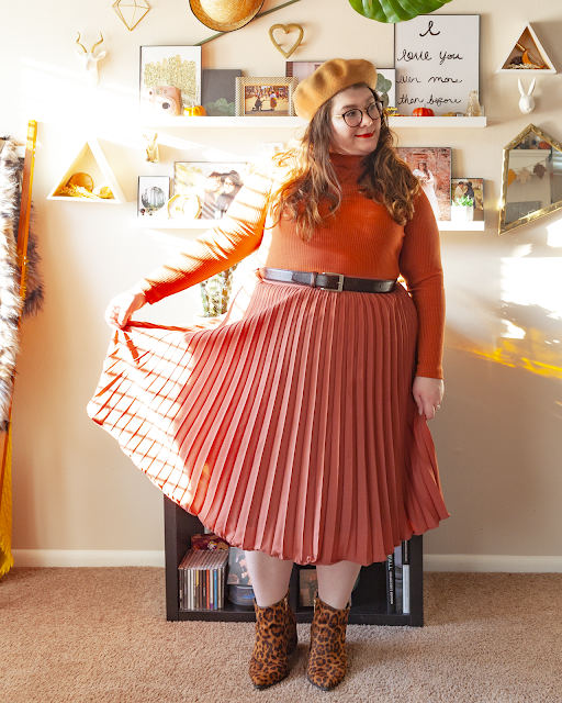 An outfit consisting of a camel brown beret, a burnt orange long sleeve ribbed mockneck to tucked into a rose colored pleated midi skirt and brown cheetah print ankle boots.