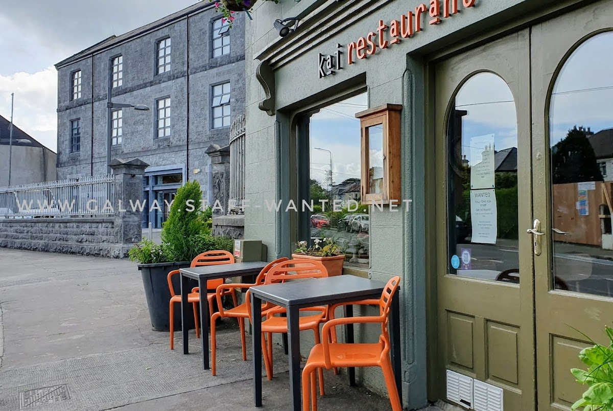 cafe in Galway's west side, next door to the Jesuit church and the main entrance to the-jes secondary school building.   Outside tables with orange chairs and outside pot plants in the background.