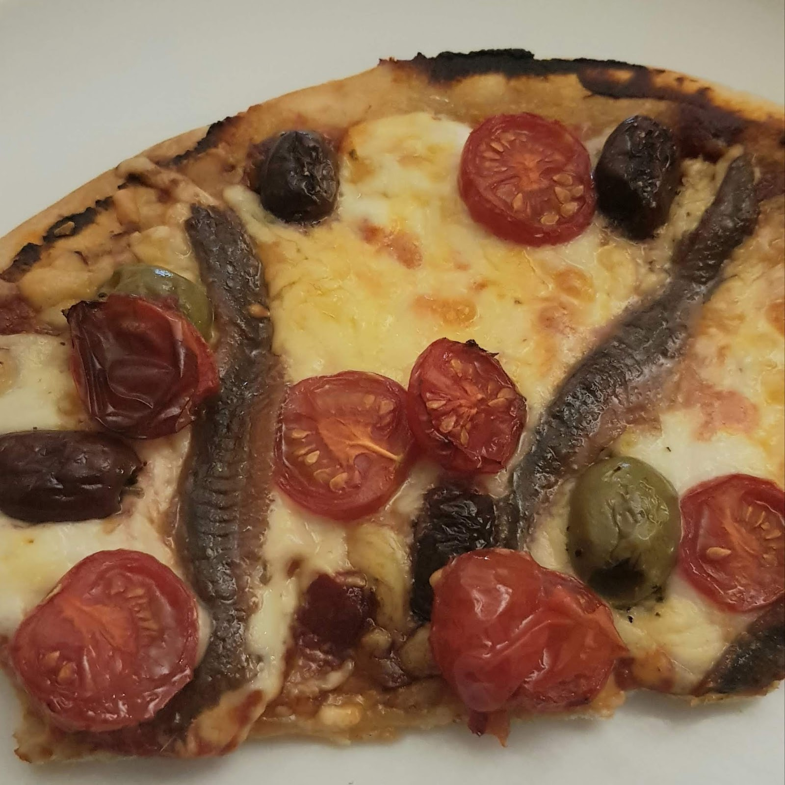 Cauliflower base pizza with mozzarella, anchovies and tomatoes