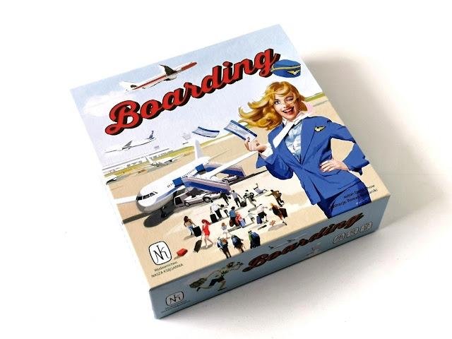 na zdjęciu pudełko gry boarding, na którym widzimy stewardessę mrugającą do nas okiem a w tle pasażerów wsiadających do samolotu