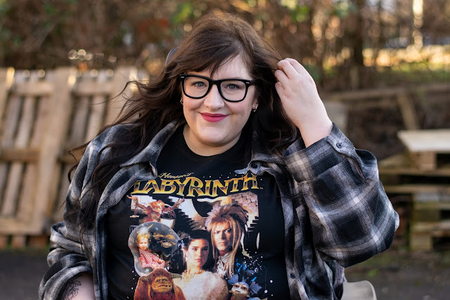 Woman in wheelchair smiling and holding hair back whilst wearing Labyrinth tshirt