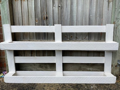 Pallet painted white for tin can flower pots