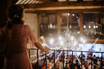 Novia mirando a los invitados desde una barandilla