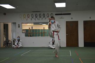 A martial arts teenager doing a front kick