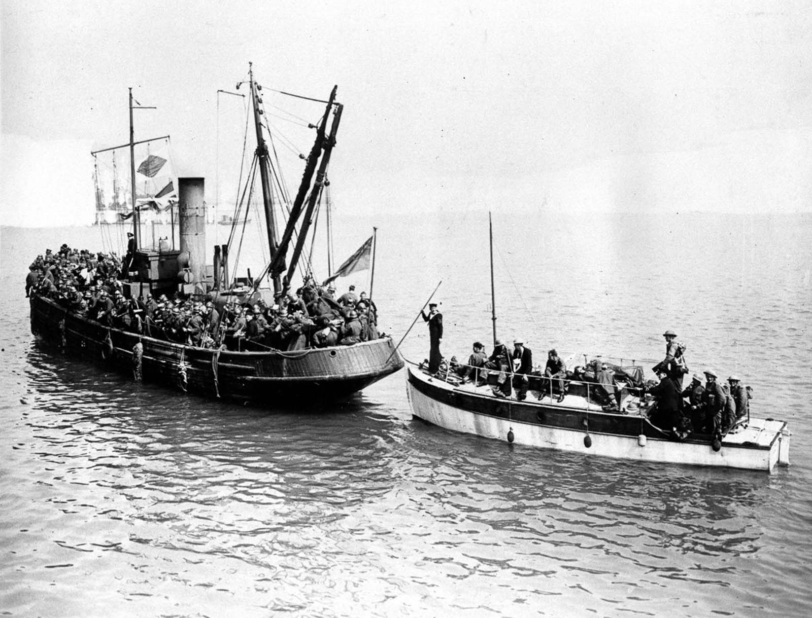 Some of the last troops to be evacuated crowd aboard two civilian boats.