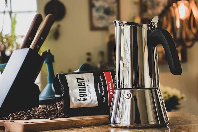 Cafeteira italiana Bialetti ao lado de café em grãos