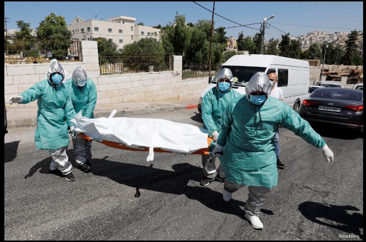 Personal médico palestino carga el cuerpo de una persona fallecida a causa del coronavirus para ser enterrado en un cementerio en Hebrón. 29 de junio de 2020 / REUTERS
