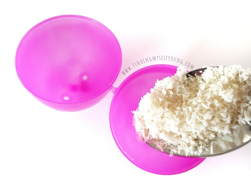 filling a plastic easter egg with coconut