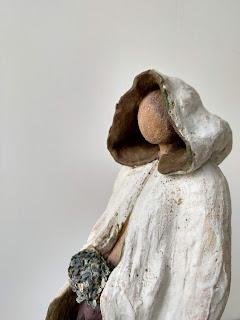 Escultura de cerámica de una mujer con capa