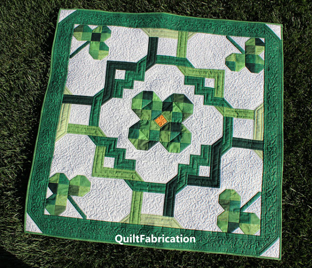 five clover quilt laying on grass