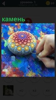 Осуществляется роспись красками камня кисточкой разными узорами