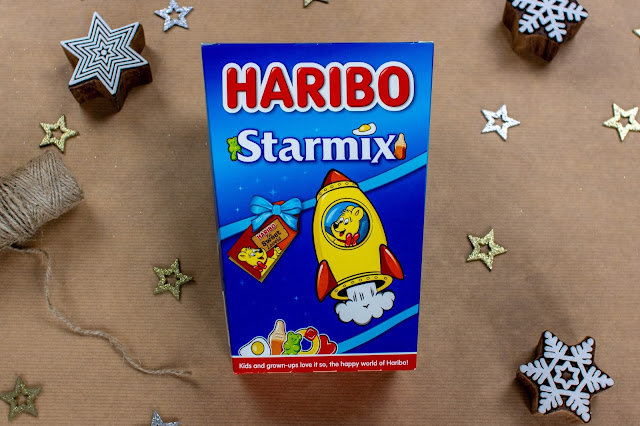 A 380g gift box of Haribo Starmix on wrapping paper surrounded by stars and twine ready to be wrapped as a gift for a Tween