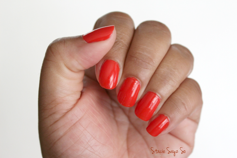 a woman's hand with orange nail polish