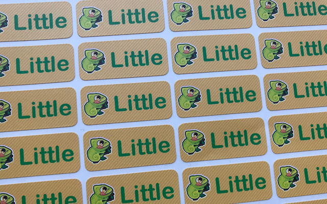 "A sheet of coloured name labels in yellow with green writing saying ""Little"" next to a chameleon"
