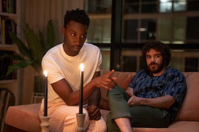 Two men, one Black and one white, tell a story in front of a candle
