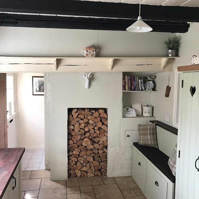 cottage kitchen inspiration featuring log filled fireplace and Emma Bridgewater collection