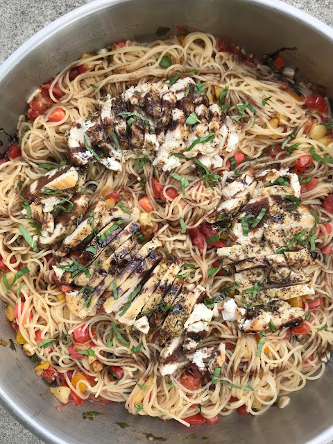 Skillet with finished bruschetta chicken pasta.