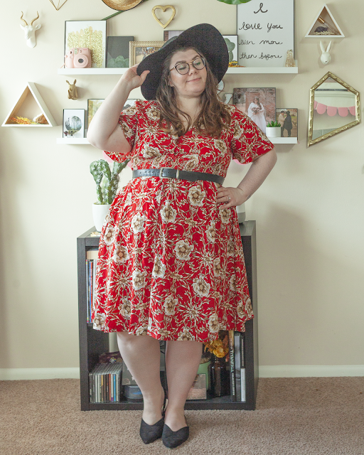 An outfit consisting of a black wide brim hat, a short sleeved red floral midi dress belted with a black belt and black pointed toe slingback flats.