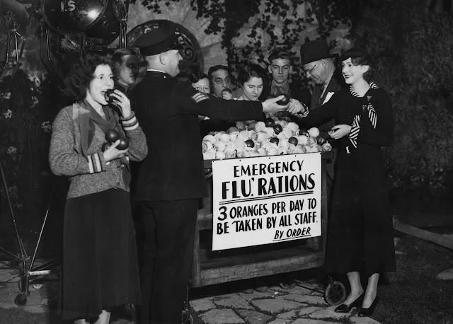 """İngiliz aktris Molly Lamont (en sağda), 1940 dolaylarında Londra'daki Elstree Stüdyoları'nda portakal """"acil grip ilaçları"""" alıyor."""