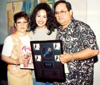 Selena feliz posando con su disco junto a su mamá y papá
