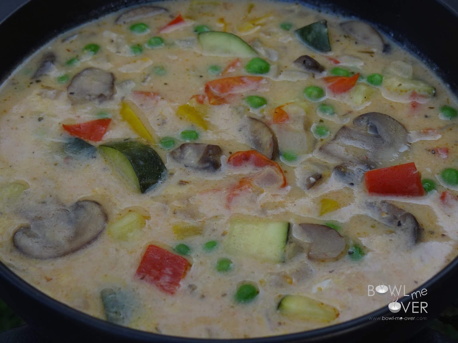 A delicious vegetable soup filled with zucchini, mushrooms, peppers, onions, and peas in a creamy, cheesy broth.