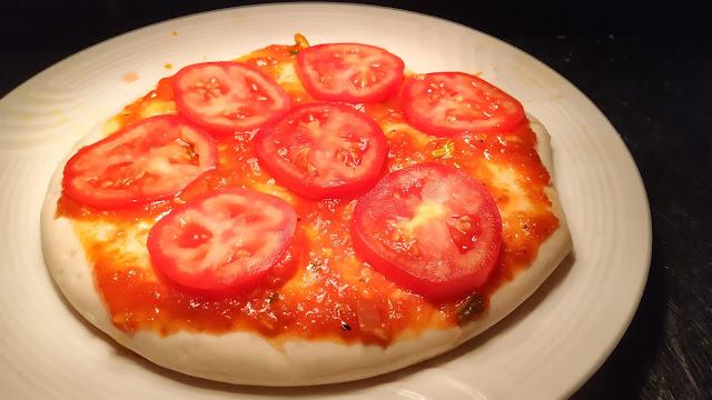 Slice tomatoes over sauce spread pizza bread base for pizza Recipe