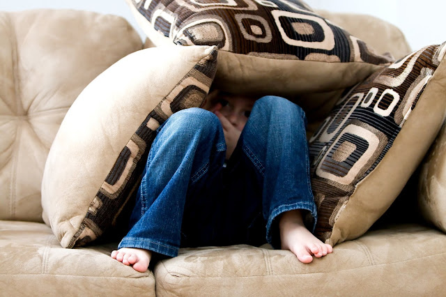 A child hiding between cushions on a sofa seeming frightened.
