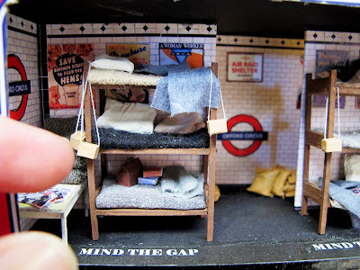 Miniature scene of a three-tier bunk in an underground shelter set up in a 1940s tube station. with fingers for scale.
