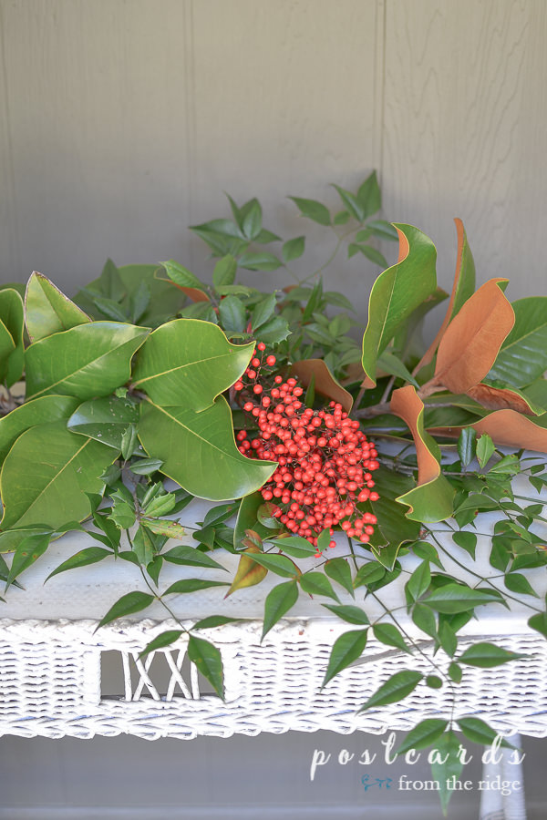 white wicker table with fresh magnolia leaves, holly, and nandina