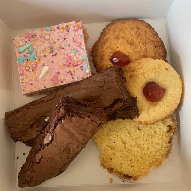 Treat box containing brownie, melting moment, unicorn krispie and lemon drizzle loaf slice