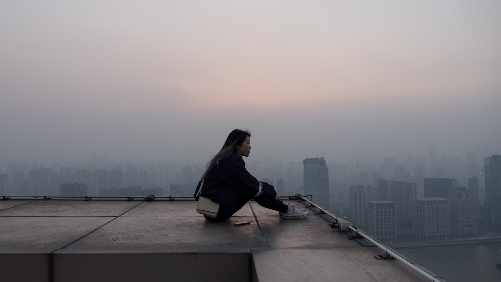 a girl sitting on top of a flat roof