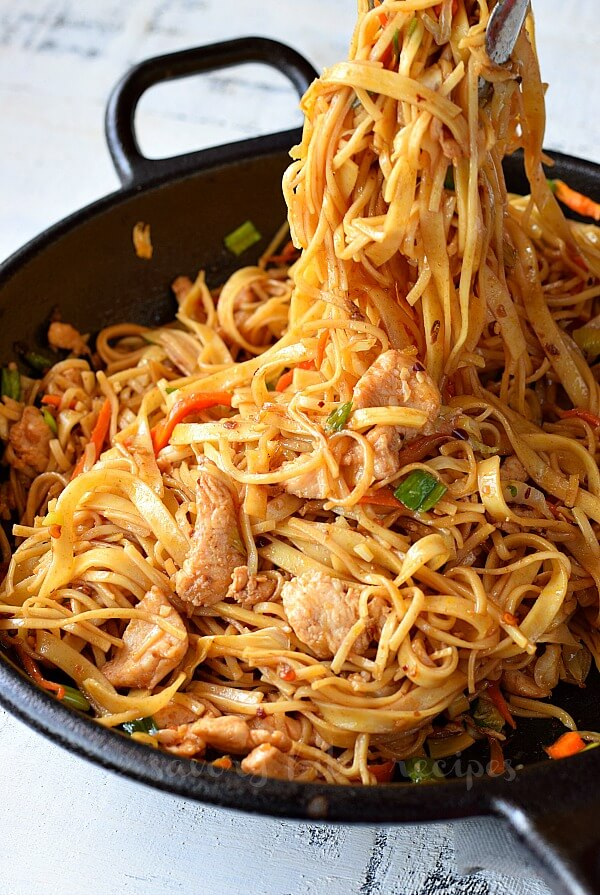 a wok with delicious spicy noodles and chicken stir fry