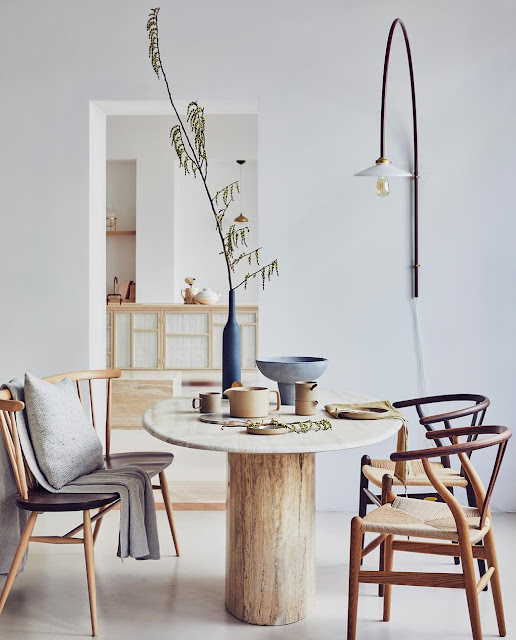 scandinavian breakfast space with a wood pedestal round dining table, cherner chairs, and neutral styling