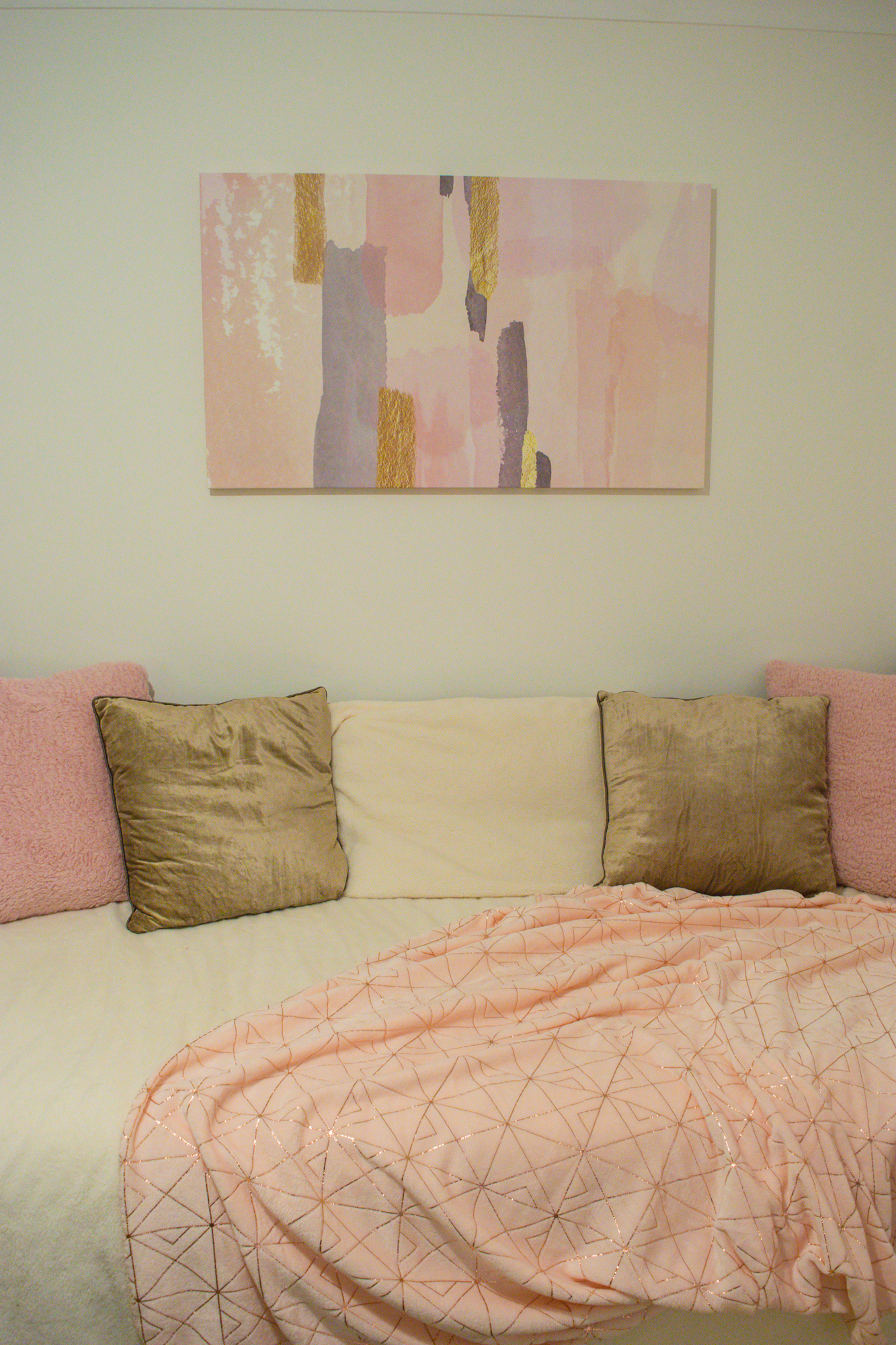Pink and gold printed canvas above a black framed bed.