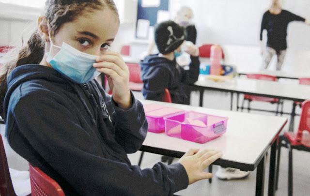 Menina com mascara em sala de aula