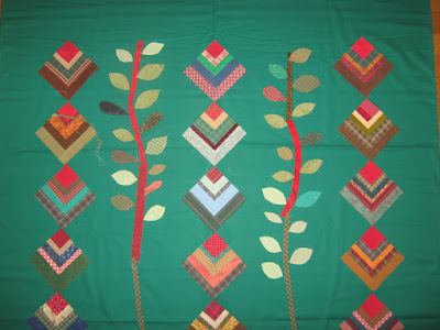 quarter log cabin blocks in possible string layout with vines and leaves