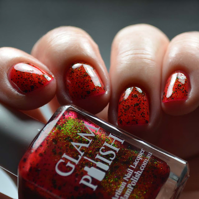 red nail polish with glitter shown in low light