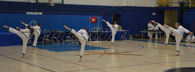 Martial arts black belts doing a high Taekwondo roundhouse kick
