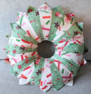 green and white dresden plate christmas fabric wreath filled with stuffing, looks like a cushion without a bow